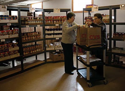 Shelly Weatherholt picks up groceries at the food pantry to stock a new resident's home.