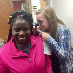 Charleston High School student Kressa Sweeney uses an otoscope to examine homeschooled student Anagrace Karrick at the October 2016 Health CareeRx Club event at the Sarah Bush Lincoln Neoga Clinic.